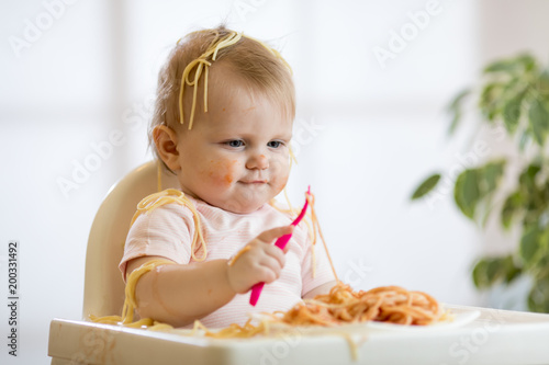 adorable one-year baby toddler try to catch a pasta - 200331492