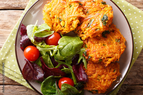 Foto Murales Freshly made crispy fritters from sweet potato and fresh vegetable salad close-up. horizontal top view