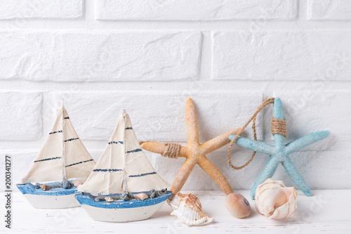 Dekoracyjne łodzie, muszle i gwiazdy morza w pobliżu przez biały mur.