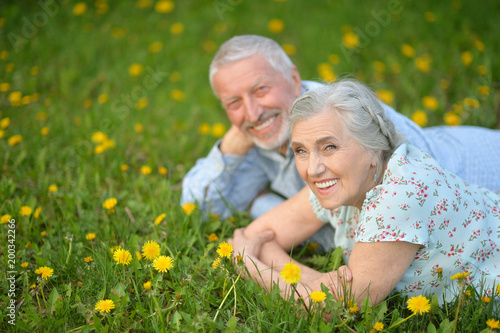 Senior couple lying on green meadow with dandelions - 200342266