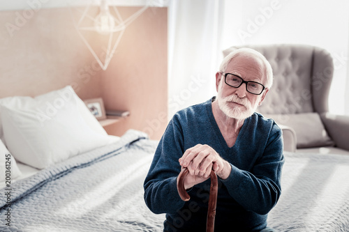 At home. Pleasant nice senior man sitting in the bedroom and holding his walking stick while resting at home