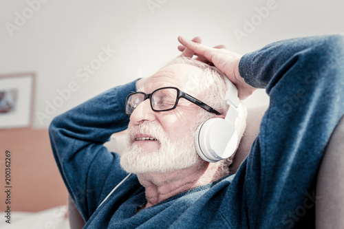 Pleasant pastime. Delighted nice elderly man sitting in the armchair and listening to music while enjoying his rest