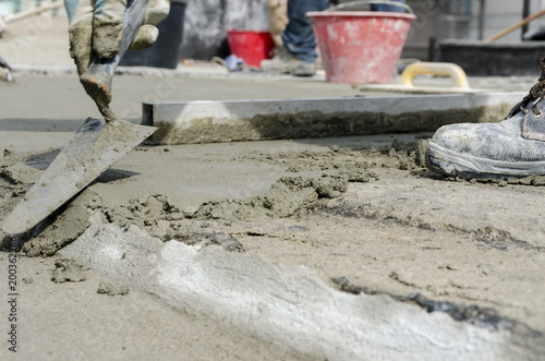 worker who throws cement on a building site for the renovation of a roof