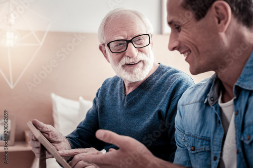 Pleasant communication. Cheerful nice pleasant smiling and talking to his grandfather while spending time with him