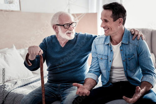 Time together. Happy nice young man smiling and talking while spending time with his father