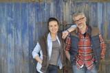 Couple of farmers standing in front of barn wooden door - 200366674