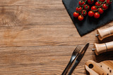 top view of fresh ripe tomatoes on slate board, fork with knife, seasonings in containers and peppercorns on wooden table - 200367608