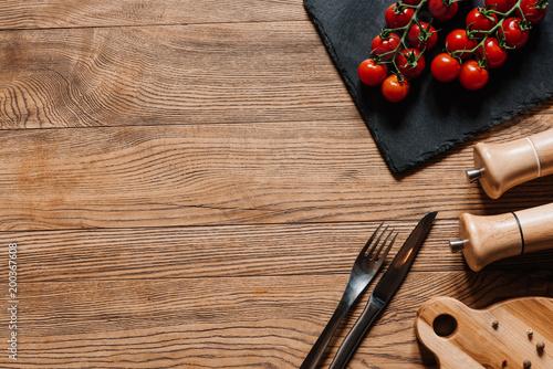 widok z góry świeżych dojrzałych pomidorów na tabliczce łupkowej, widelec z nożem, przyprawy w pojemnikach i pieprzu na drewnianym stole