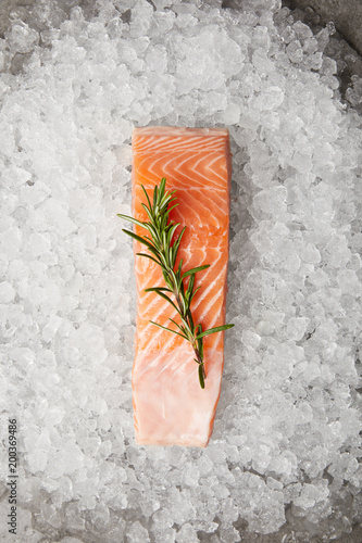 top view of slice of red fish with rosemary branch on crushed ice