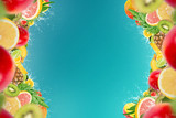 Tropical fruits with water splash on blue background, empty space in the middle