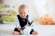 Cute little toddler boy, dressed smart casual, playing with little black and white rabbit - 200376037