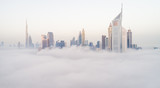 Aerial view of Dubai's skyscrapers in the clouds.