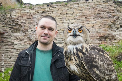 A man holds an owl in the hands of a grass and an old stone wall.