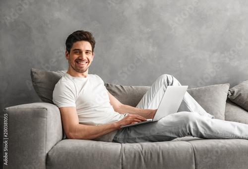 Kaukaski zarośnięty mężczyzna lat 30-tych w odzież casual za pomocą notebooka, leżąc na wygodnej kanapie w szarym mieszkaniu