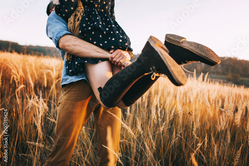 Foto Murales handsome guy with a beard in a blue denim shirt gentle hugs, hand holding and kissing a girl with blond hair in a blue dress and yellow scarf in a field at sunset. stylish couple