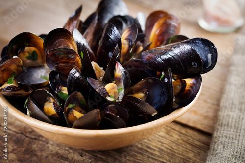 Fototapeta Black mussels on plate with green on wooden board