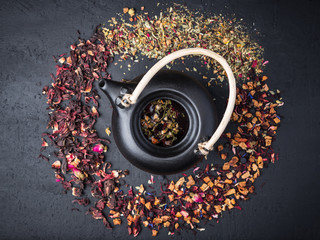 Black ceramic teapot with tea,Different tea on dark concrete background. © olegkoval