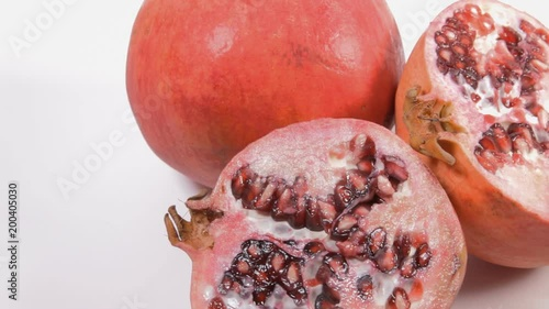 Some pomegranate fruits, both whole and halves, on a rotating surface. Close-up shot.