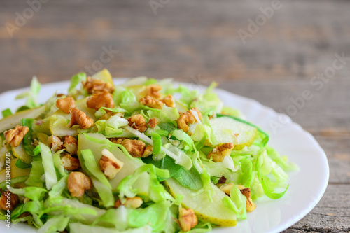Pear cabbage slaw recipe. Simple salad with raw pear, cabbage and walnuts on a plate. Rustic wooden background. Clean eating. Closeup