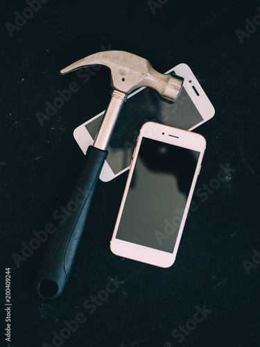broken screen of smartphone with hammer on black table