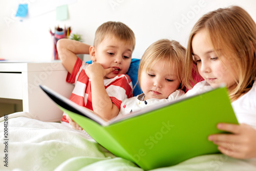 Foto Murales childhood, leisure and family concept - little kids reading book in bed at home