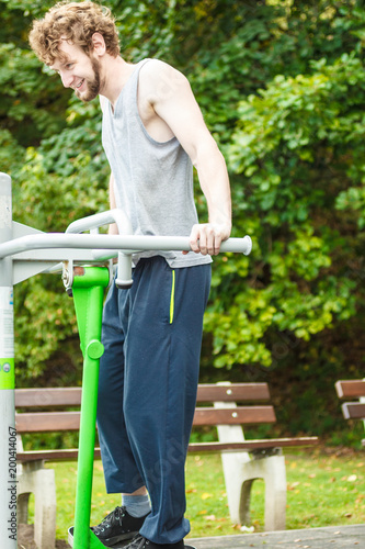 Poster Active man exercising on ski trainer outdoor.