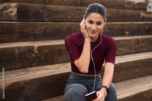 Smiling brunette with ear phones sitting on stairs