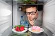Mann hat die Wahl zwischen Süßigkeiten und Obst