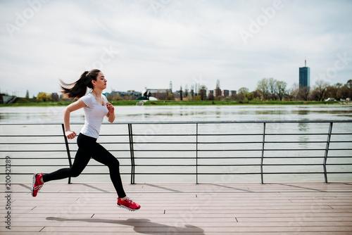 Fototapeta Motivated sportswoman running near the river.