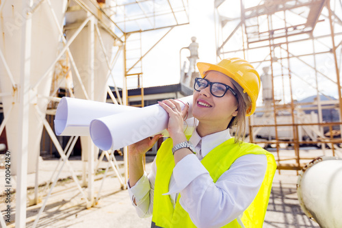 Happy female industrial worker with blueprints