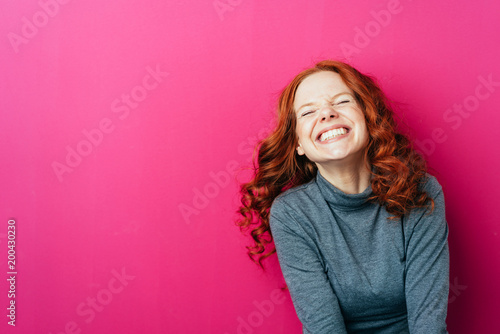 Leinwanddruck Bild Young laughing woman against pink background