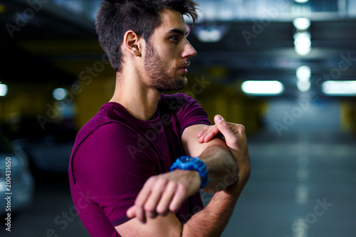 Young male runner stretching his muscles before workout in the underground car parking. - 200431650