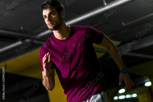Portrait of young male athlete running in the underground car parking.
