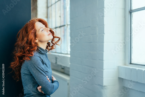Foto Murales Young redhead woman standing daydreaming