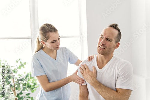 men Explaining Shoulder injury to the doctor