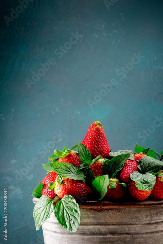 erdbeeren im blecheimer vor blau grünen hintergrund