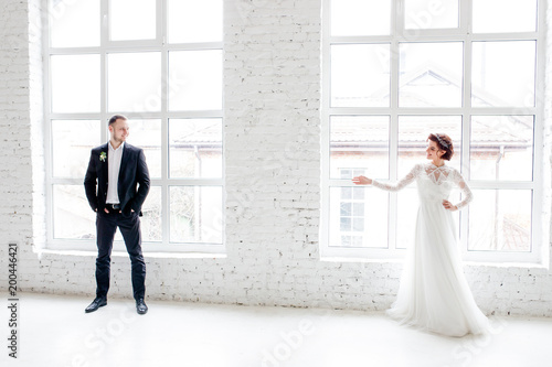 Bride and groom standing on white wall background © Yuliia