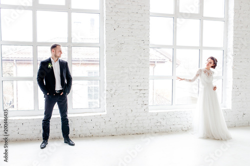 The bride and groom standing by the big window in the studio with a white interior. © Yuliia