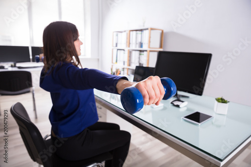 Foto op Aluminium School de yoga Businesswoman Doing Exercise With Dumbbell