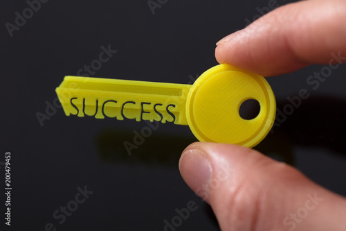Businessperson's Hand Holding Yellow Key