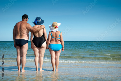 three elderly people stand on the seashore holding hands, look at the horizon resting sunbathing bathing suits swimming trunks, straw hat beach shore sand summer weekend vacation - 200493673