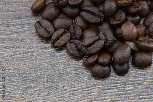 Foto op Aluminium Koffiebonen Coffee beans on a dark background and a wooden table. Closeup.