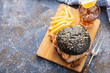 Black burger with fish and shrimps. Fishburger with prawns, top view.
