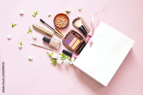 Various cosmetic products eye shadow powder lip gloss blush mascara brush for makeup and white spring flowers in a white gift bag on a pink pastel background top view with copy space