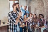 Business people making team training exercise during team building seminar singing karaoke. - 200500841