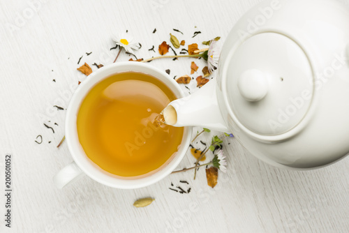 pouring tea with teapot into cup on white table © winston
