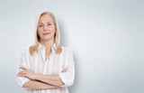 Attractive middle aged woman with folded arms on grey background - 200502048