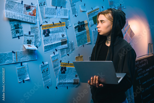 female hacker with laptop standing in front of wall with newspaper clippings