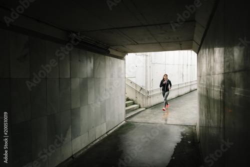 Fototapeta Urban sporty woman running in the city. Female athlete training outside in rainy winter.