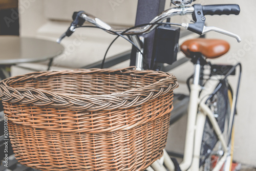 Foto op Plexiglas Fiets Healthy transport concept. Vintage bicycle left near cafe with old wooden basket in Italy, Milan. Close up.